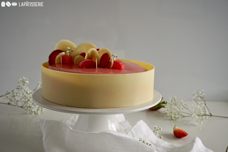 Umrahmt von einem Ring aus weißer Schokolade, verbirgt sich dahinter eine Mousse aus Erdbeeren und ein Rhabarberkompott.