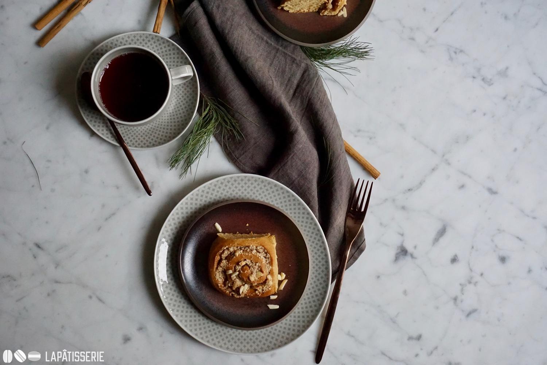 Eine Tasse Tee und ein süße Schnecke mit Mandeln und Ahornsirup.